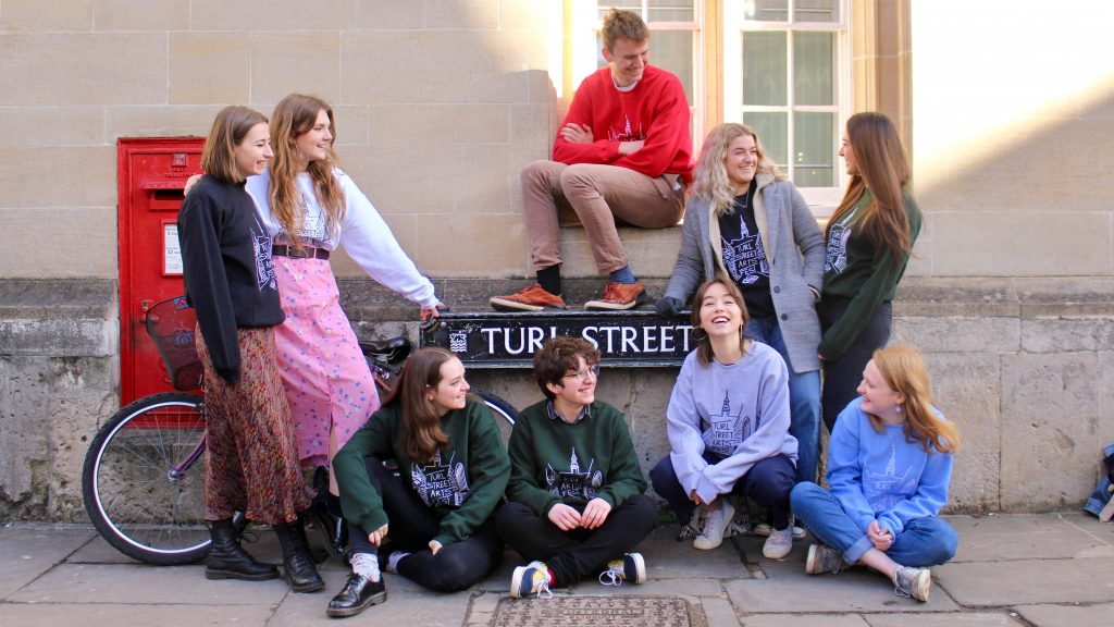 Students lean on turl Street Sign