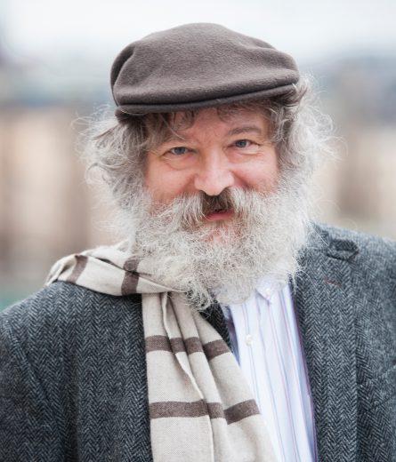 Bearded man in flat cap smiling